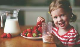 Happy child girl drinks milk and eats strawberries in summer home kitchen. Happy child girl drinks milk and eats strawberries in the summer home kitchen Stock Photos