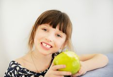 Happy child girl eating apple at home Stock Photography