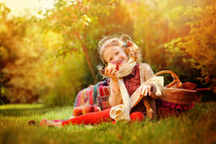 Happy child girl eating apple in sunny autumn garden Stock Photo