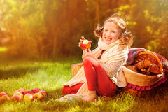 Happy child girl eating apples in autumn sunny garden Royalty Free Stock Images