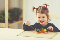 Happy child girl  eating vegetables and laughs Stock Photos