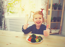 Happy child girl eating vegetables and showing thumbs up Royalty Free Stock Images