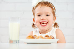 Happy child  girl eats cookies and milk Stock Photo