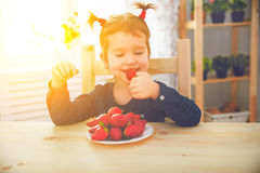 Happy child girl eats strawberries in summer home kitchen Royalty Free Stock Photography