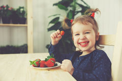 Happy child girl eats strawberries in summer home kitchen royalty free stock images