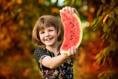 Happy child girl eats watermelon. Healthy eating concept stock images