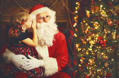 Happy child girl embraces Santa Claus, and tells him secret Royalty Free Stock Photo