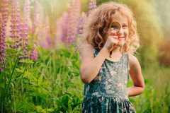 Happy child girl exploring nature with loupe on summer walk Royalty Free Stock Images