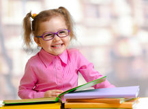 Happy child girl in eyeglasses reading book royalty free stock photos