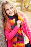 Happy child girl with fallen golden leaves Royalty Free Stock Photos