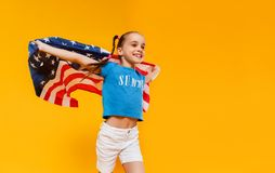 Happy child girl with flag of   United States of America USA on yellow   background stock photo