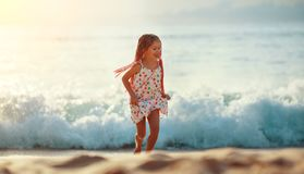 Happy child girl with flying hair dancing and runing on beach at sunset stock photography