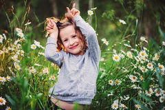 Happy child girl fooling on summer sunset field with chamomile flowers Stock Photography
