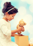 Happy child girl with gift box and teddy bear Stock Image