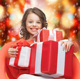 Happy child girl with gift boxes Stock Photos