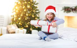 Happy child girl with gifts in bed on Christmas morning. Happy funny child girl with gifts in bed on Christmas morning stock photography