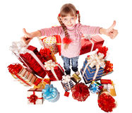 Happy child girl with group gift box thumb up. Stock Photography