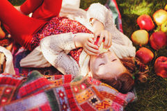 Happy child girl harvesting apples in autumn garden. Seasonal outdoor rural activity Stock Photo