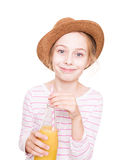 Happy child girl in a hat with a bottle of fruit juice drink Royalty Free Stock Image