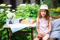 happy child girl in hat enjoying warm summer day in the blooming garden Stock Photography