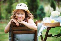 Happy child girl in hat enjoying warm summer day in the blooming garden Royalty Free Stock Image