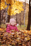 Happy child girl having fun on the autumn walk and sitting in leaves Royalty Free Stock Photo