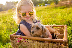Happy child girl with her dog sitting in a wicker basket Stock Photos