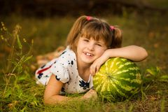 Happy child girl hold very big watermelon in sunny day. Healthy concept royalty free stock photo
