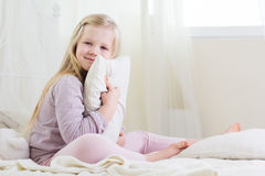 Happy child girl is holding pillow in bed Royalty Free Stock Image