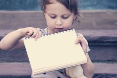 Happy child girl holding a white board with place for text. Child girl holding a white board with place for text stock photos