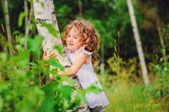 Happy child girl hug birch tree in summer forest Royalty Free Stock Images