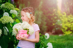 Happy child girl with hydrangea bouquet playing outdoor in cozy summer garden Royalty Free Stock Photo