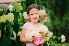 Happy child girl with hydrangea bouquet playing outdoor in cozy summer garden Royalty Free Stock Photography