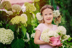 Happy child girl with hydrangea bouquet playing outdoor in cozy summer garden Royalty Free Stock Image