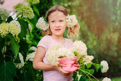 Happy child girl with hydrangea bouquet playing outdoor in cozy summer garden Royalty Free Stock Images