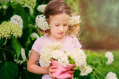 Happy child girl with hydrangea bouquet playing outdoor in cozy summer garden Stock Photos