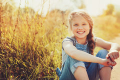 Happy child girl in jeans overall playing on sunny field Royalty Free Stock Photo