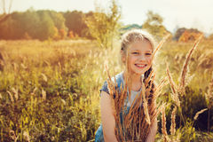 Happy child girl in jeans overall playing on sunny field, summer outdoor lifestyle Royalty Free Stock Images