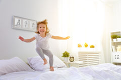 Happy child girl jumps and plays bed Royalty Free Stock Photos