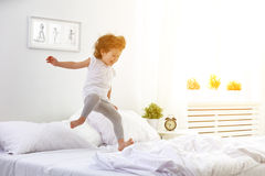 Happy child girl jumps and plays bed Royalty Free Stock Image