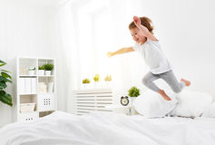 Happy child girl  jumps and plays bed Stock Photography