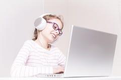 Happy child girl kid in headphones using laptop computer Stock Image