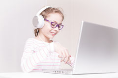Happy child girl kid in headphones using laptop computer. Eight years old, caucasian, happy smiling blond child girl kid in headphones using laptop computer stock photo