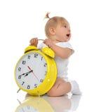 Happy child girl kid sitting with big yellow alarm clock stock photo