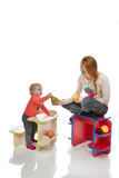 Happy child girl kid standing near little table with big yellow Stock Photo