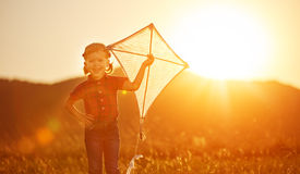 Happy child girl with a kite on meadow in summer Royalty Free Stock Photography
