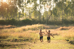 happy child girl with a kite running on meadow in summer in natu Royalty Free Stock Images