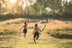 Happy child girl with a kite running on meadow in summer in nature Royalty Free Stock Image