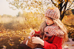 Happy child girl in knitted scarf and sweater with basket on autumn walk in forest eating apples Stock Photo