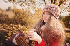 Happy child girl in knitted scarf and sweater with basket on autumn walk in forest eating apples Stock Photography